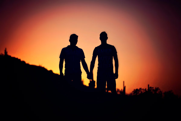 Two men hold hands, facing the sunset
