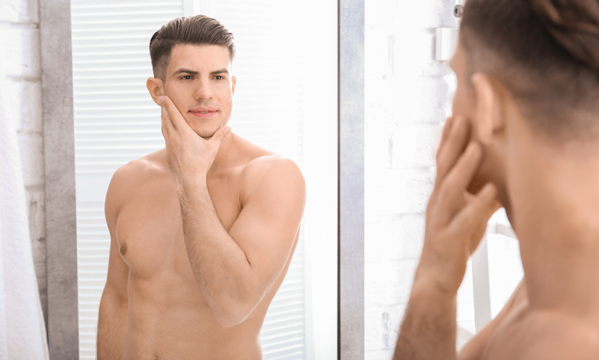 Blond Man Considers Face in Mirror
