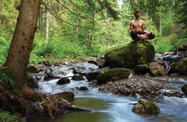 meditation on rock by stream