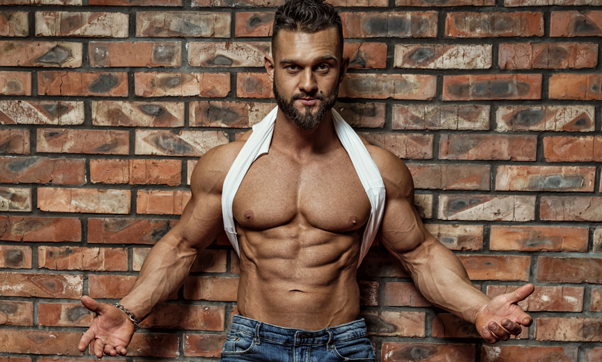 Muscular Man Against Brick Wall