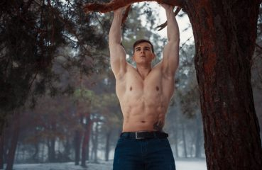 man with muscular body doing pullups outdoors
