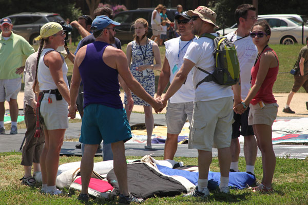 People joining hands over AIDS quilt