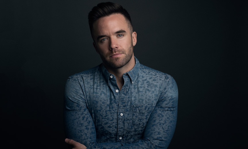 Brian Justin Crum folding his hands wearing a printed shirt
