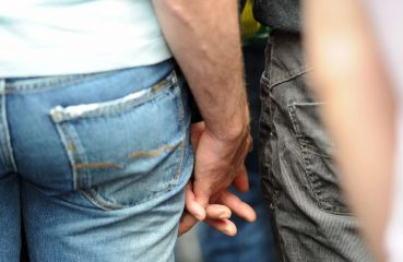 Two men holding hands at Pride