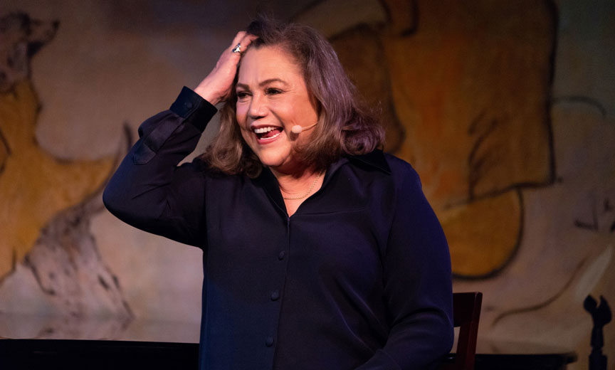 kathleen turner smiling and holding head in surprise