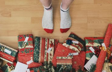 Stocking Feet Beside Christmas Presents