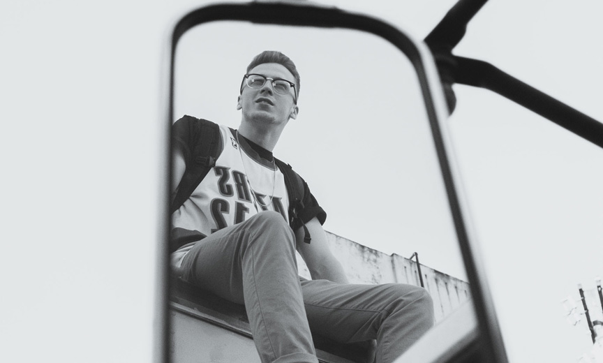Young Man Reflected in Bus Mirror