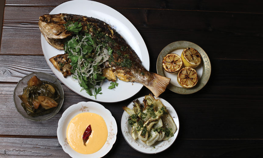 whole fish with sides of fennel and grilled lemons