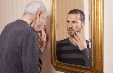 Older Man Looking in Mirror at Younger Man