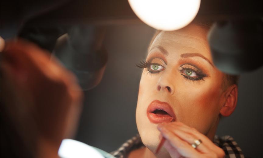 man applying drag makeup