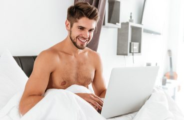 Shirtless Man Smiling at Laptop