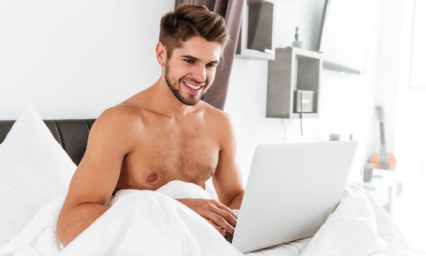 Shirtless Man Smiling at Laptop