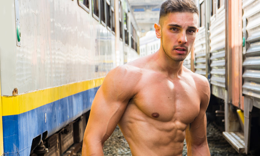 Shirtless Man Between Trains