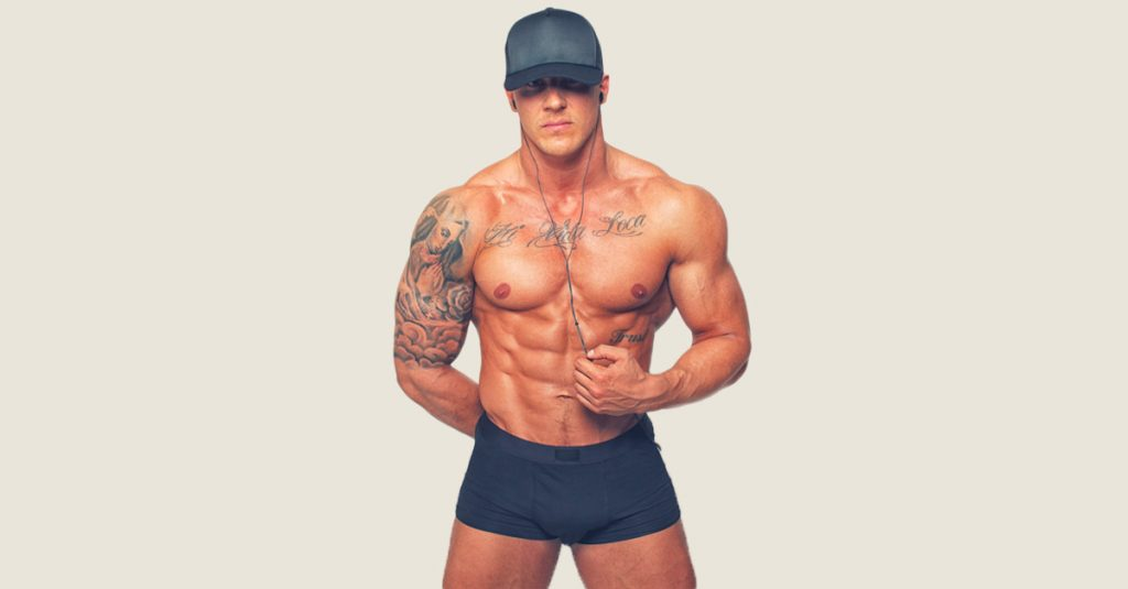 muscle guy with tattoos listing to podcast